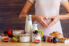 Female Make Shape Of Heart With Her Hands. Light Summer Breakfast With Organic Yogurts, Fruits, Berries And Nuts. Nutrition That Promotes Good Digestion And Functioning Of Gastrointestinal Tract.
