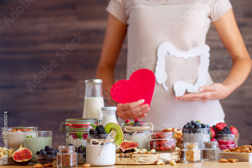 Obraz Female is holding figures of heart and intestines. Summer breakfast with organic yogurts fruits, berries and nuts. Nutrition that promotes good digestion and functioning of gastrointestinal tract. - fototapety do salonu