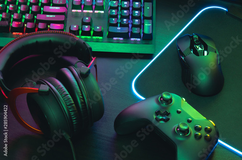 gamer work space concept, top view a gaming gear, mouse, keyboard, joystick, headset, mobile joystick, in ear headphone and mouse pad on black table background Canvas Print