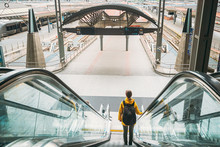 Oslo, Norway. Young Adult Caucasian Woman Visiting Oslo Central Station Railway Station. Woman Backpacker Tourist Goes Down To Trains Platform On Escalator