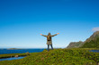 A man with backpack enjoys landscape. Mountain and ocean. Scenic view. Beautiful nature. Green grass, blue sky. Outdoor leisure activity, hiking. Wanderlust. Adventure, lifestyle. Explore North Norway