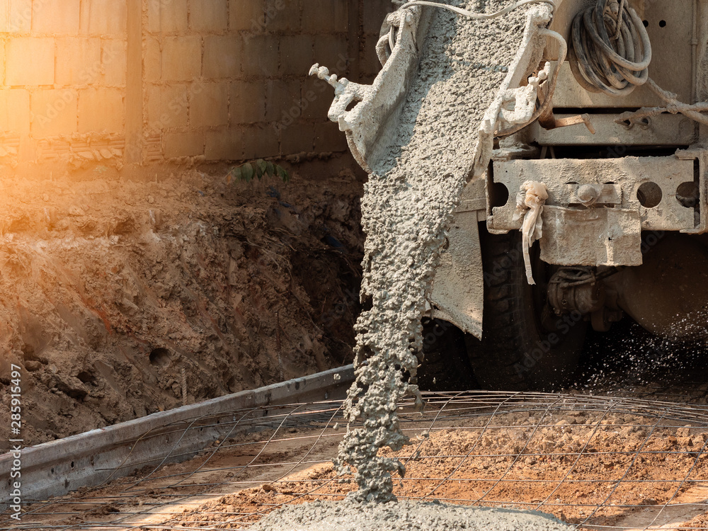 Fototapeta Pouring ready-mixed concrete after placing steel reinforcement to make the road by mixing in construction site