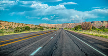 Arid Landscape Of Arizona. The Crumbling Sandstone Mountains And The Highway