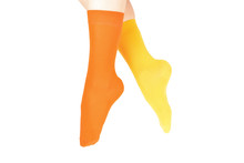 Yellow And Orange Socks On Woman Foot Isolated On White Background.