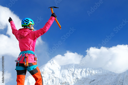 Papiers peints Glisse hiver Happy Woman Climber in bright pink jacket reaches the summit of mountain peak enjoying the landscape view.