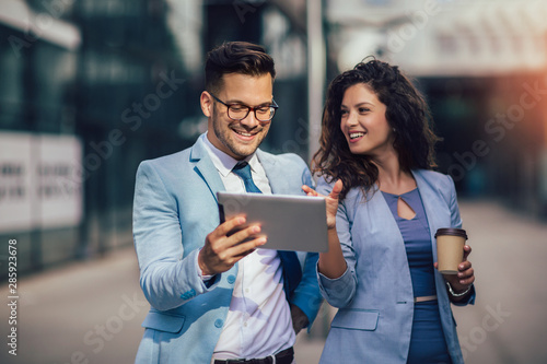 Fotografia  Handsome man and beautiful woman as business partners using digital tablet outdo
