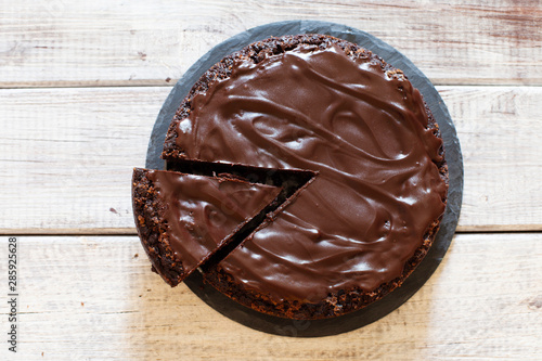 Fotografia Chocolate brownie cake with ganashe topping on gray background