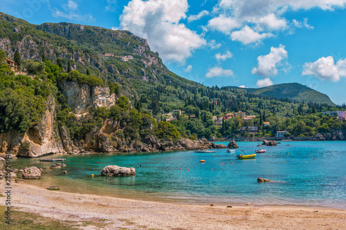 Foto auf Leinwand Khaki Beautiful landscape with sea–lagoon with turquoise water, mountains and cliffs, green trees, blooming bushes and flowers, colorful boats and rocks in a blue water. Corfu Island, Greece.