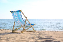 Empty Cozy Lounger On Sand Near Sea, Space For Text. Beach Objects