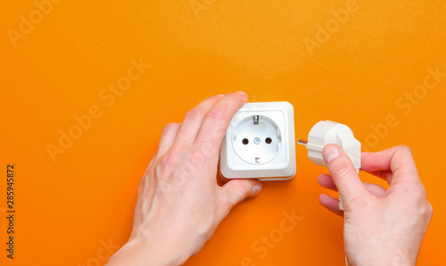 Obraz Female hands plug in power plug into electro outlet on orange background. Minimalism. Top view - fototapety do salonu