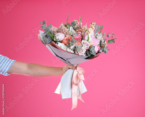 Fotografía Man holding beautiful flower bouquet on pink background, closeup