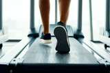 Close up male muscular feet in sneakers running on the treadmill at gym
