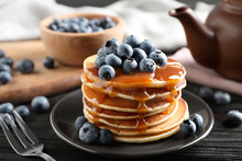 Delicious Pancakes With Fresh Blueberries And Caramel Syrup On Black Wooden Table