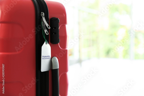 Photo Stylish suitcase with travel insurance label on blurred background, closeup