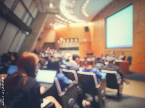 Blur of auditorium room use for present meeting background.