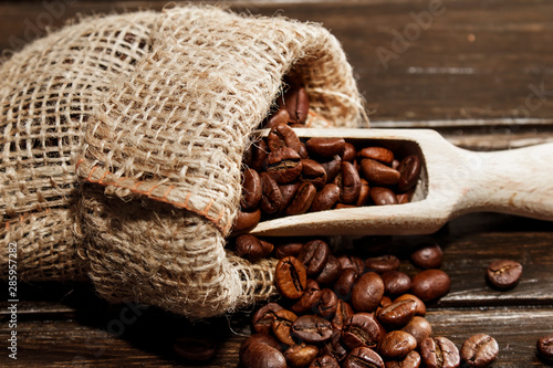 Coffee beans in hemp bag on a brown wood background