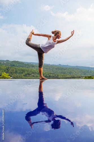 Fotografie, Obraz  Caucasian woman practicing yoga by the pool