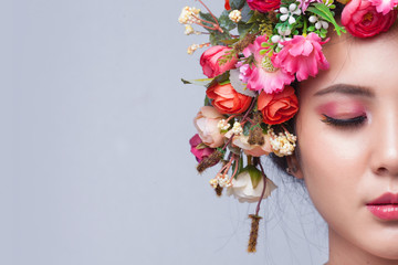 Close up of beautiful young asian woman with flowers. Brunette woman with lux...