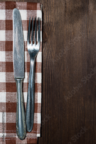 cutlery on a kitchen napkin, wooden background for recipes, vertical top view
