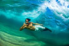 Men Swim Underwater Behind A B...