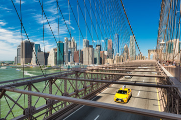 Yellow taxi on the Brooklyn Bridge, New York
