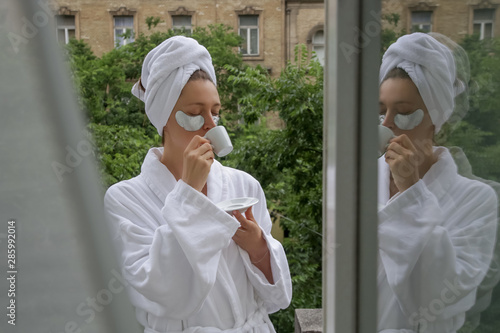 Woman in a bathrobe and wrapped head towel enjoying her morning at the balcony, Fototapet