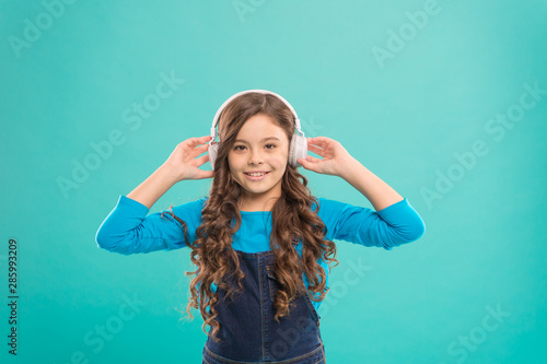 Sound of the childhood. Adorable little girl listening to sound track on blue background. Cute small child wearing headphones playing electronic sound. Relaxing with melodious sound - 285993209