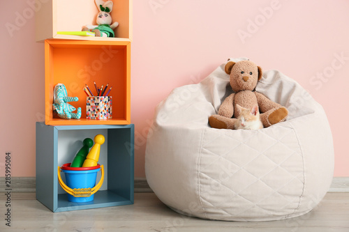 Adorable kitten with teddy bear on beanbag chair in room Wallpaper Mural