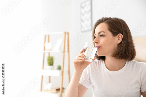 Morning of beautiful young woman drinking water in bedroom Wallpaper Mural