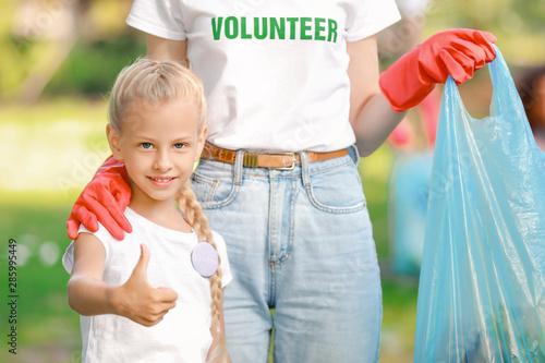 Little volunteer with woman gathering garbage in park Wallpaper Mural