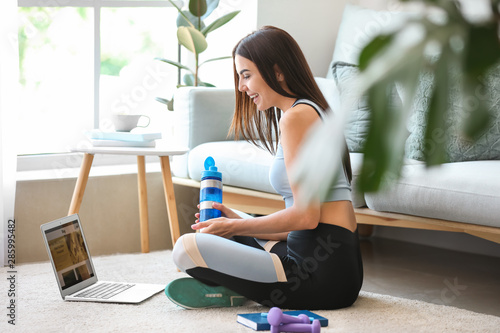 Female sport blogger with laptop at home