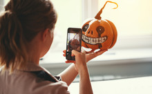 Woman Artist Prepares For Halloween And Photographed On Smartphone His Work Painted Pumpkin.