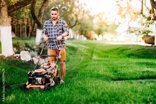 Fotografia Portrait of young gardener using lawn mower for grass cutting in garden