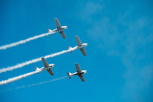 Airplanes With White Smoke Traces On Air Show. Pilots Make Tricks On Jets At Blue Sky Background