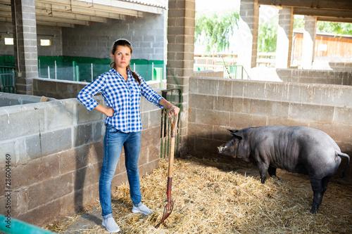 Portrait of female farmer feeding iberian pigs on farm Canvas Print