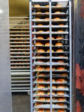 Freshly Baked Bread Rolls On A Baker's Shelf Trolley At A Bakery.