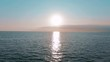 Aerial 4k view. Stunning sunset sun over the sea. Beautiful cinematic scene. Golden sun sets over the horizon, flying above the surface of the water