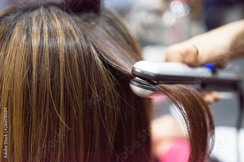 Hairdresser using hair straightener on brown-haired woman