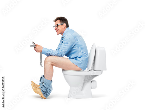 Valokuva  Man with a tablet pc in glasses, a shirt and a tie strains while sitting on the toilet, isolated on white background