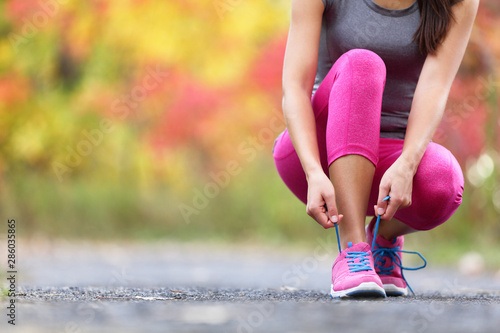 fototapeta na drzwi i meble Autumn running shoes girl tying laces ready to run in forest foliage background. Sport runner woman training cardio in outdoor fall nature in pink activewear leggings and footwear.