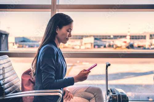 Obraz Airport phone travel Asian businesswoman using mobile smartphone in business class lounge waiting for plane flight texting sms message. Technology and travel people VIP lifestyle. - fototapety do salonu