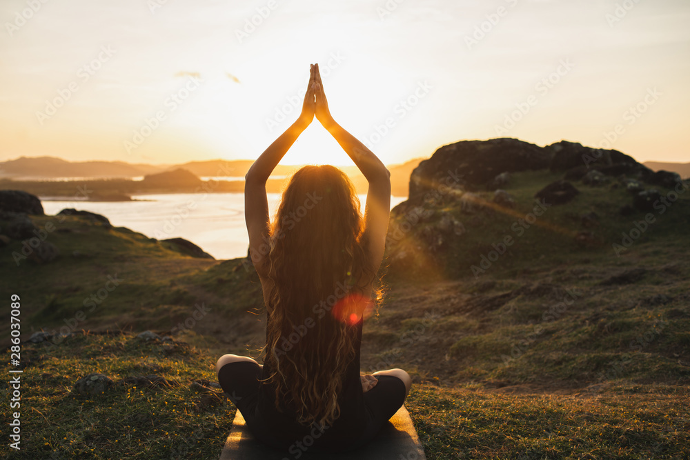 Fototapety, obrazy: Young woman practicing yoga outdoors. Spiritual harmony, introspection and well-being concept. Landscape background