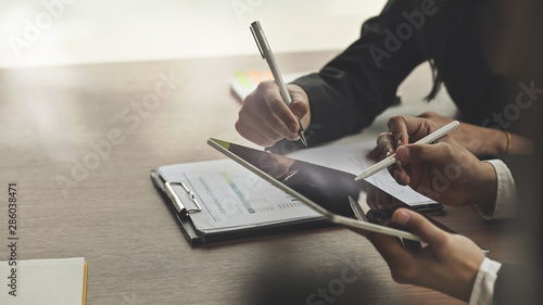 Cuadros en Lienzo Closeup shot business consult with tablet and paperwork.