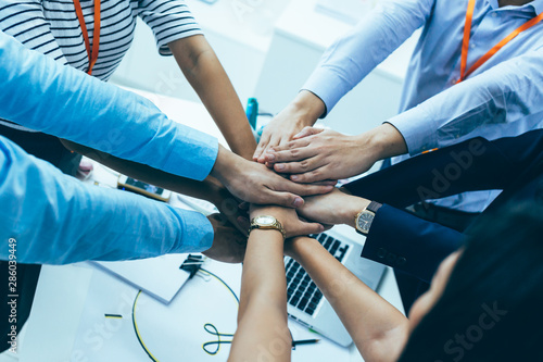 Fényképezés  Young Asian business people gathering and putting hands together in meeting room