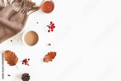 Autumn composition. Cup of coffee, scarf, dried leaves, flowers, rowan berries on white background. Autumn, fall, thanksgiving day concept. Flat lay, top view, copy space