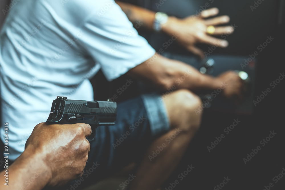 Fototapeta Armed robber using the gun to robbery the money with safe background.