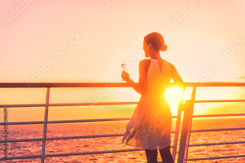 Fototapeta Luxury cruise ship travel elegant woman drinking glass of champagne enjoying watching sunset from boat deck over ocean in Europe destination vacation. Cruising sailing away on holiday. obraz na płótnie