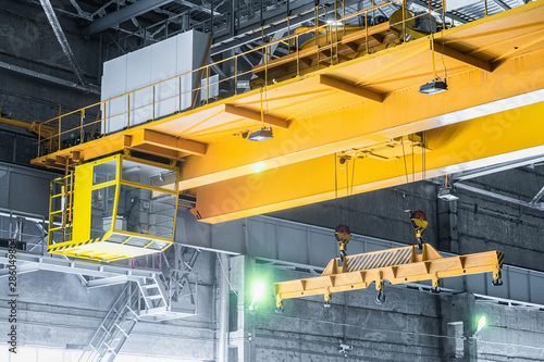Photo Yellow overhead crane with linear traverse and hooks in engineering plant shop