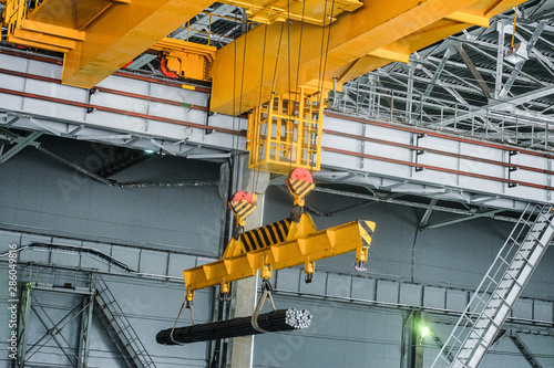 Obraz na płótnie Yellow overhead crane carries cargo in engineering plant shop