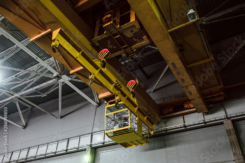 Yellow overhead crane with linear traverse and hooks in engineering plant shop Wallpaper Mural